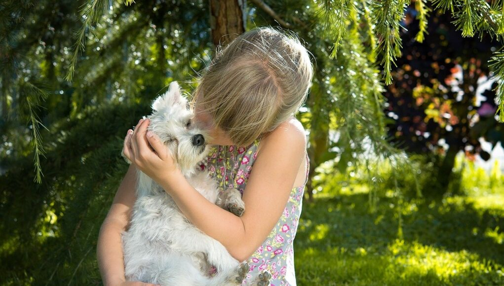a young girl kissing her dog