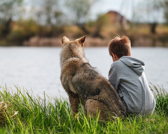a kid and a dog sitting together along the river