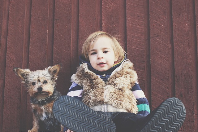 young kid an his dog sitting together