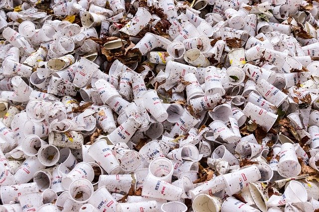 Lots of white dirty paper cups scattered around over dirt