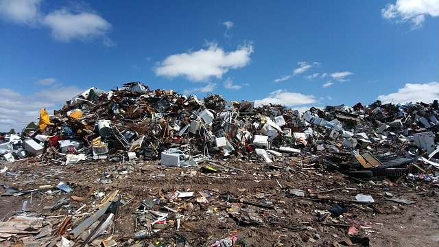 Scrap yard with trash piled up under a blue sky with clouds