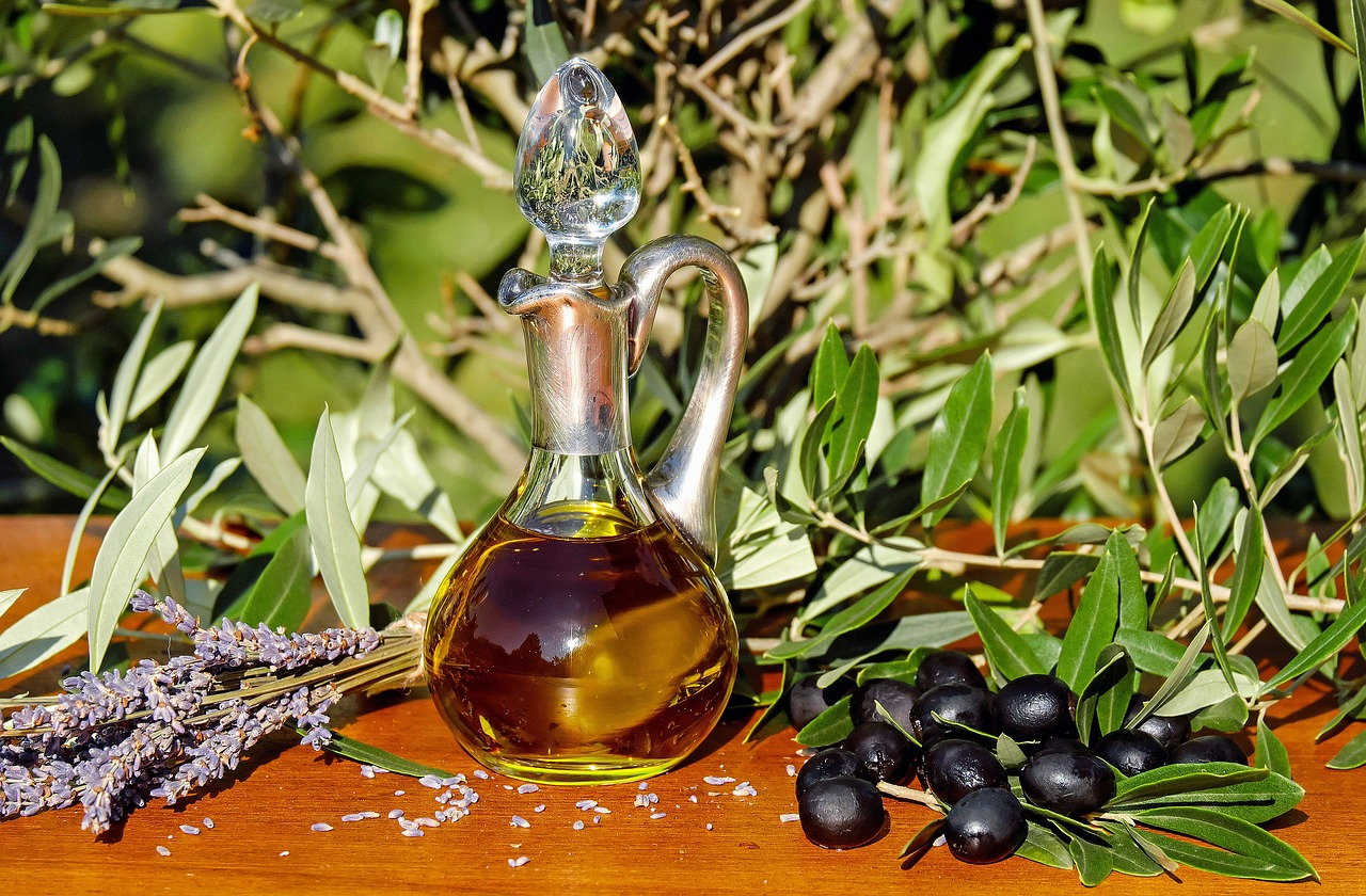 a glass bottle with olive oil, olives and lavander - olive oil for dogs cover